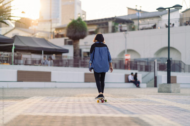 attractive young asian woman skating in Kobe Japan