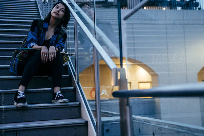 attractive young female skater relaxing on stairs