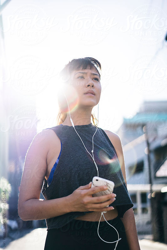 Fit Asian woman jogging in a city