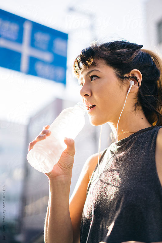 Asian woman drinking a bottle of water after running