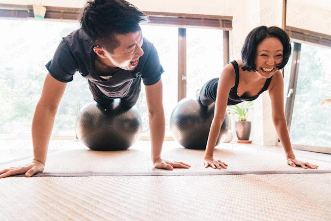 Japanese woman performing Yoga with help of personal trainer